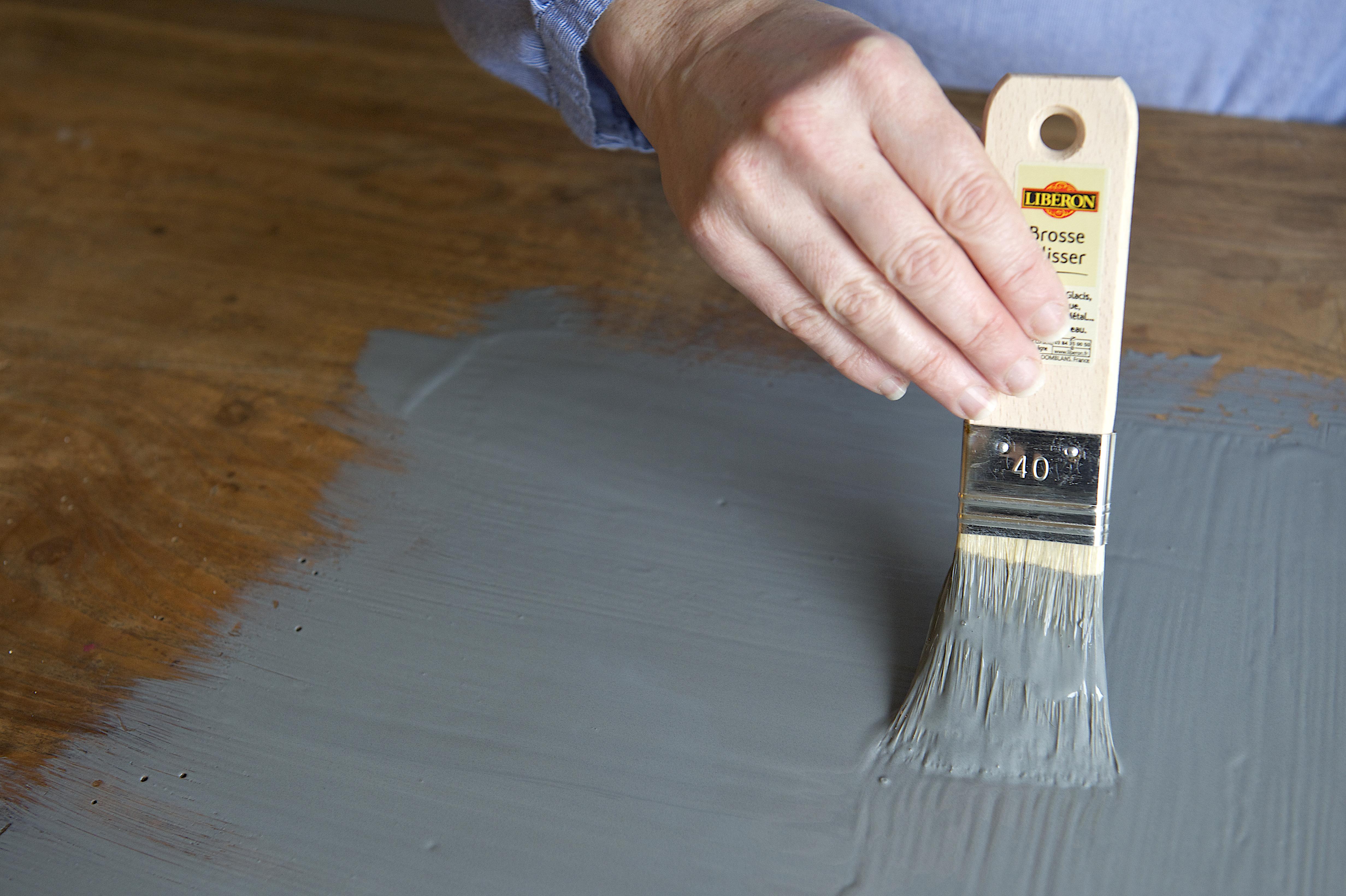 Servez-vous d'un papier de verre pour frotter le plateau en suivant le sens des fibres du bois. Ensuite, après avoir enlevé les poussières, enduisez la partie de la peinture à effet ardoise, puis passez un coup de chiffon après le séchage.
